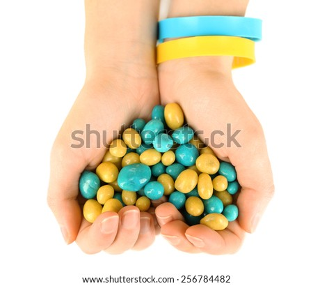 Hands with blue-yellow candies - colors of flag of Ukraine, isolated on white - stock photo