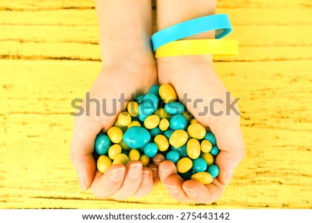 Hands with blue-yellow candies - colors of flag of Ukraine, on wooden background - stock photo