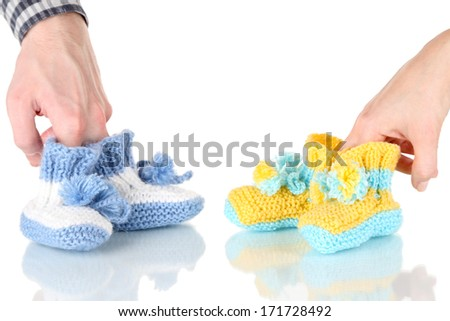 Hands with crocheted booties for baby, isolated on white - stock photo