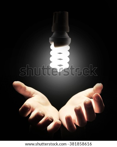 Hands with energy saving light bulb on black background - stock photo