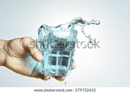 hands with glass and water splashing  - stock photo