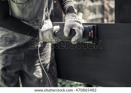 hands with gloves holding sander machine, polishing black wood surface, saturated color tone
