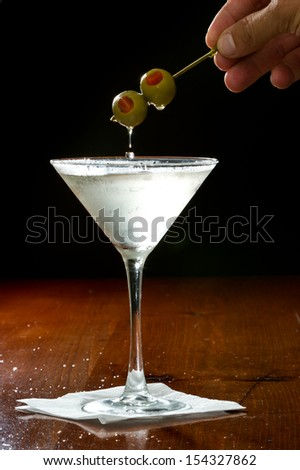 hands with green cocktail olives over a martini glass
