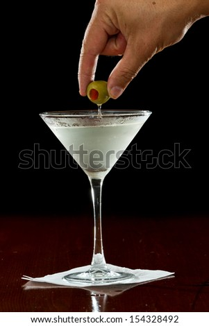 hands with green cocktail olives over a martini glass - stock photo