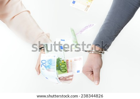 Hands with handcuffs with money in background - stock photo