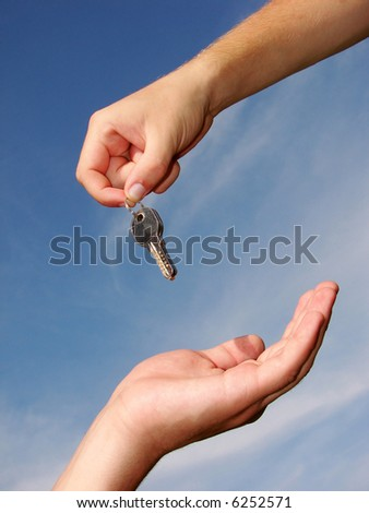 Hands with key on a background sky
