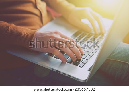 hands with laptop typing in sunlight - stock photo