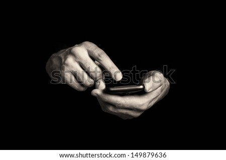 hands with mobile smartphone. Man typing text message on mobile phone, focus on hands and the phone device. - stock photo