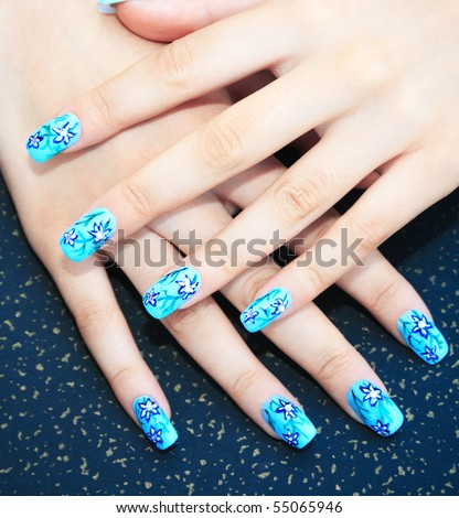 Hands with nail art on spotted background. - stock photo
