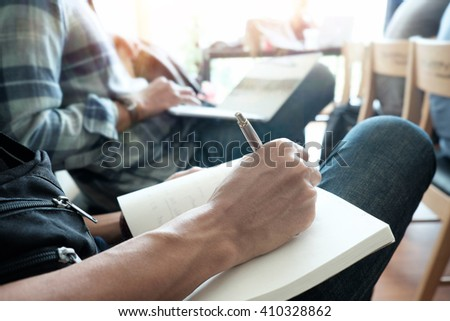 hands with pen writing on notebook in classroom,vintage effect. - stock photo