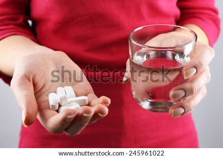 Hands with pills and glass of water  - stock photo