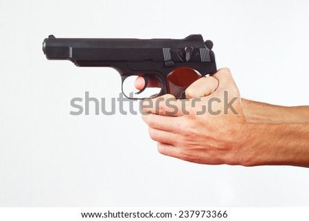 Hands with pistol on a white background - stock photo