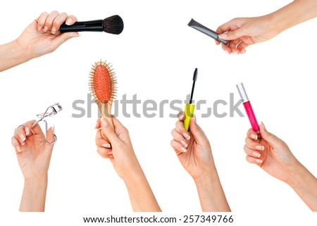 Hands with professional cosmetics for makeup: brush, eye primer, mascara, lip booster, comb - stock photo