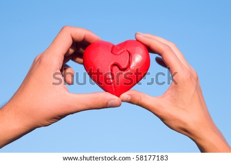 Hands with puzzle heart in sky - stock photo