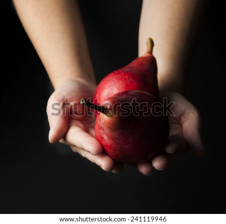 Hands with red anjou pears