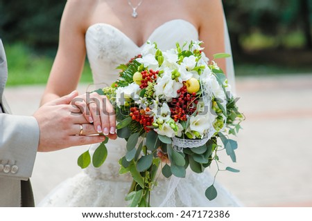 hands with rings bride and groom with wedding bouquet. - stock photo