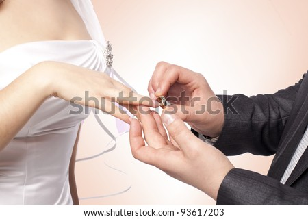Hands with rings Groom putting golden ring on bride's finger during wedding ceremony Loving couple closeup in studio isolated portrait on white background - stock photo