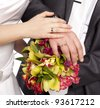Hands with rings-Hands of bride and groom and rings with wedding bouquet loving couple closeup in studio isolated portrait on white background - stock photo