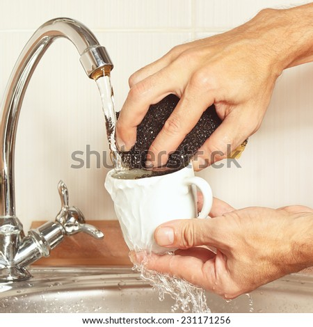 Hands with sponge wash the cup under running water in the kitchen - stock photo