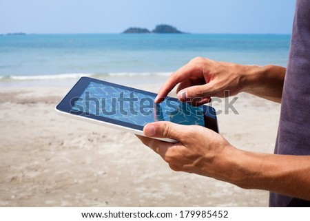 hands with tablet on the beach - stock photo