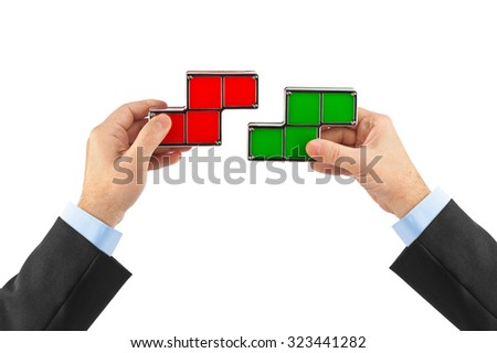 Hands with tetris toy blocks isolated on white background - stock photo