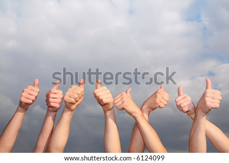 hands with the raised thumbs against the background of the cloud sky