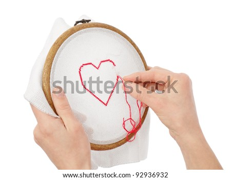 hands with tissue, embroidering red heart - stock photo