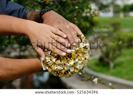 Hands with wedding ring in origami bouquet