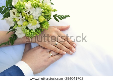 Hands with wedding rings and bouquet - stock photo