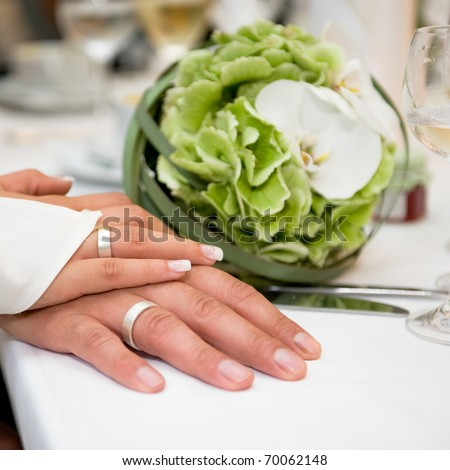 Hands with wedding rings in white gold and wedding flower bouquet on the table - stock photo