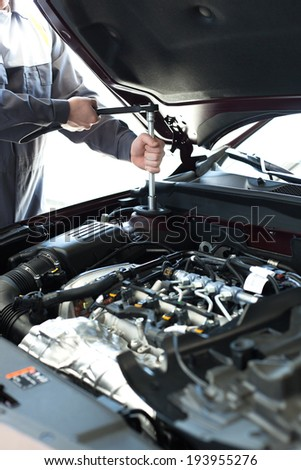 Hands with wrench on engine. Auto mechanic in car repair - stock photo