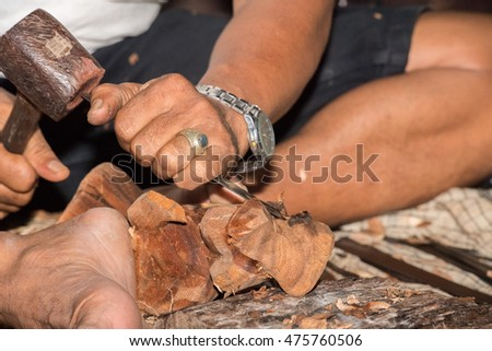 hands working and carving wood close up in bali indonesia