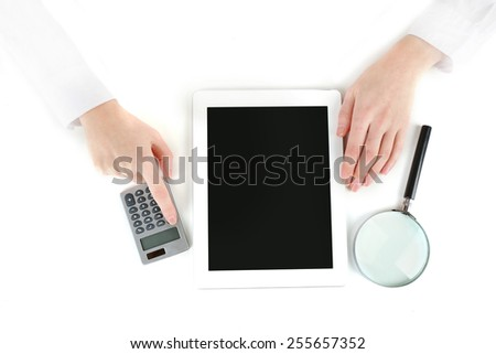 Hands working in the office with laptop and calculator, on white background - stock photo