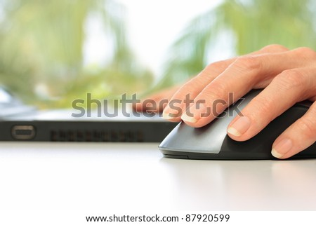 Hands Working on Laptop Computer and Mouse