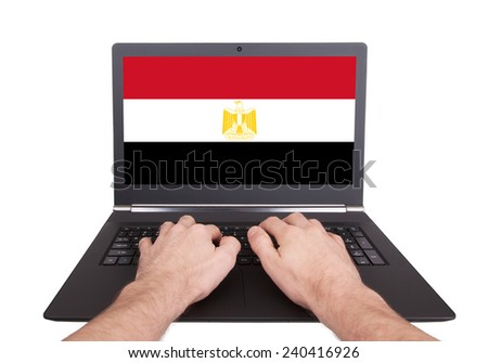 Hands working on laptop showing on the screen the flag of Egypt - stock photo