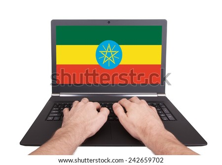 Hands working on laptop showing on the screen the flag of Ethiopia - stock photo