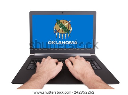 Hands working on laptop showing on the screen the flag of Oklahoma - stock photo