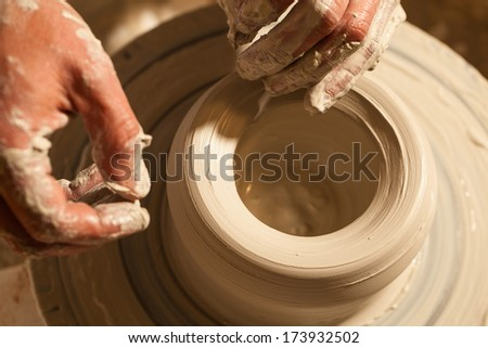 Hands working on pottery wheel , close up  - stock photo