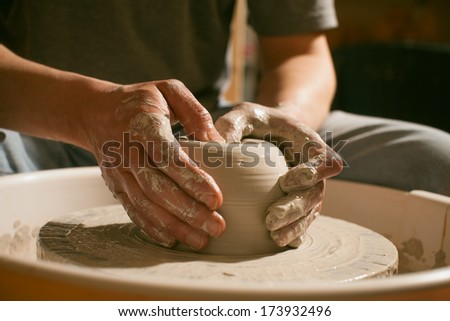 Hands working on pottery wheel , close up retro style toned  - stock photo