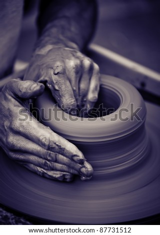 Hands working on pottery wheel , close up retro style toned photo wit shallow DOF - stock photo