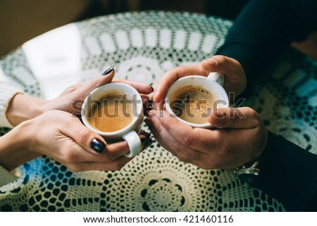 hands wrapped around a cups of coffee - stock photo