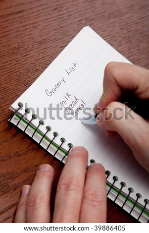 Hands writing a shopping list with a wooden desk background - stock photo