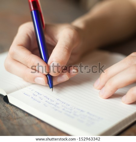 hands writing in the notepad - stock photo