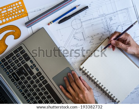 Hands writing on notepad with part of architectural blueprint / tools and laptop - stock photo