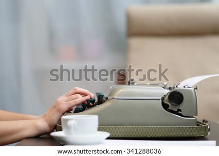 Hands writing on old typewriter near white cup - stock photo