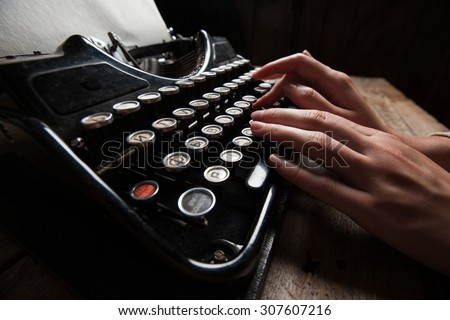 Hands writing on old typewriter over wooden table background - stock photo