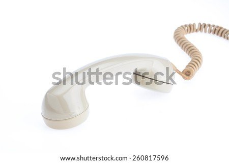 handset of antique telephone placed on isolate white background beside telephone machine - stock photo