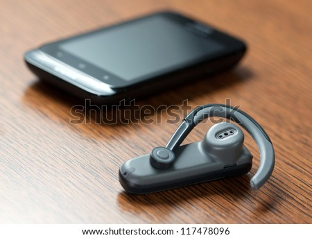 Handsfree with mobile phone in background - stock photo