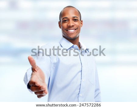 Handshake. African-American businessman over blue office background - stock photo