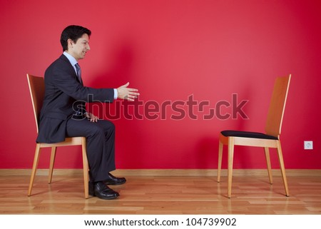 Handshake agreement between a businessman and an chair next to a red wall - stock photo